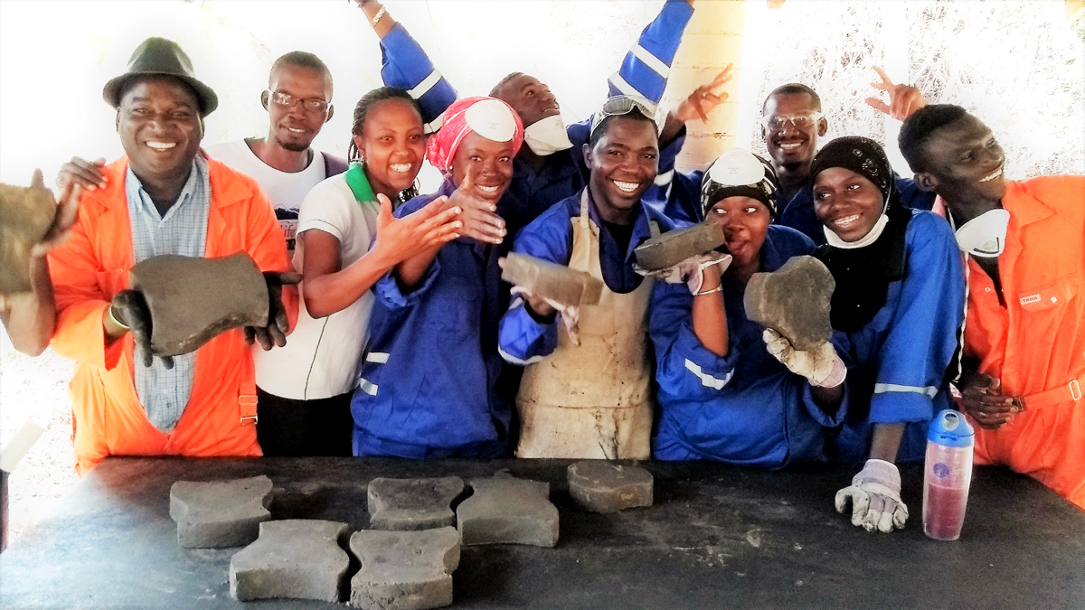 WasteAid volunteers learn how to make plastic paving tiles from waste