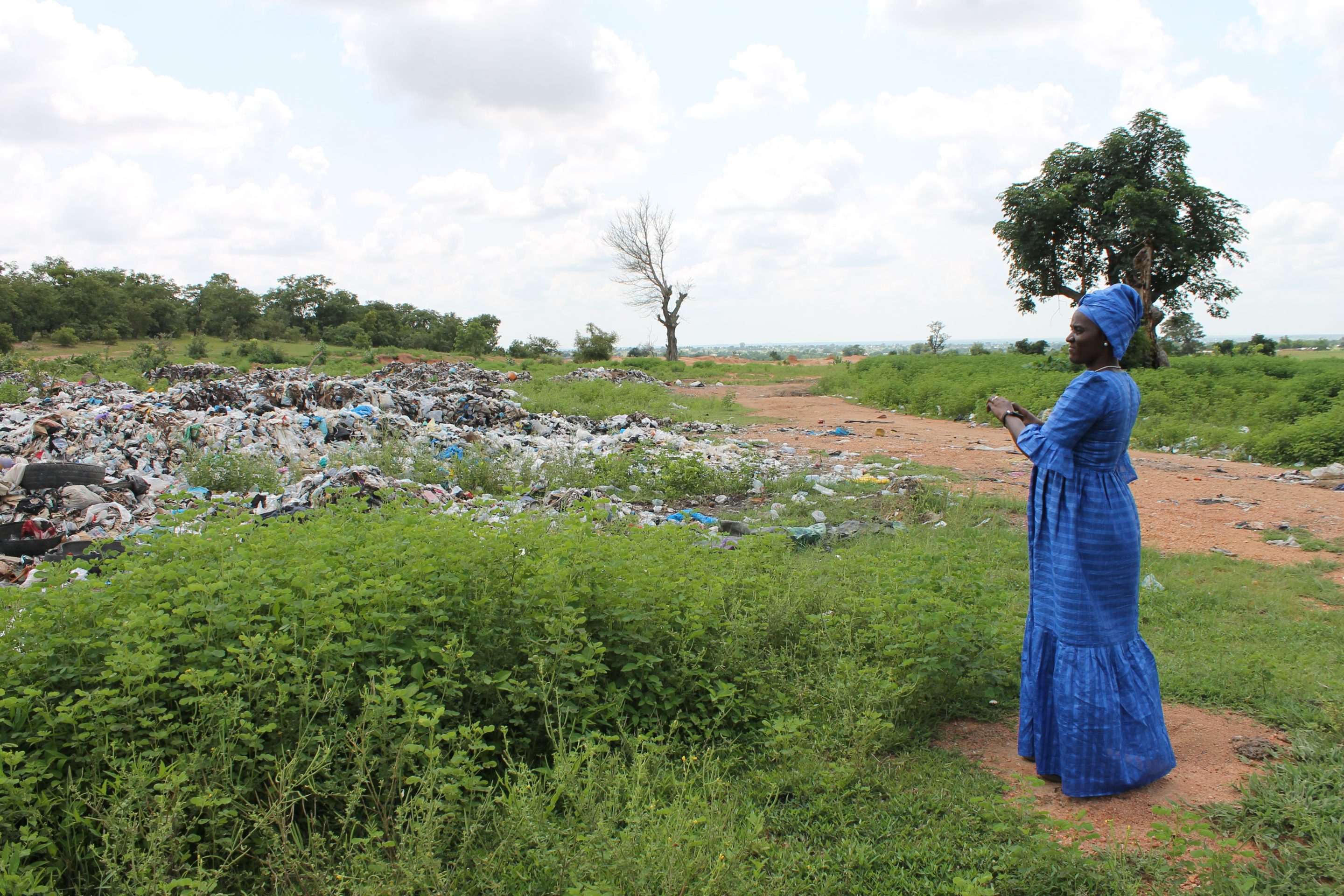 Isatou Ceesay stands next to an open dump