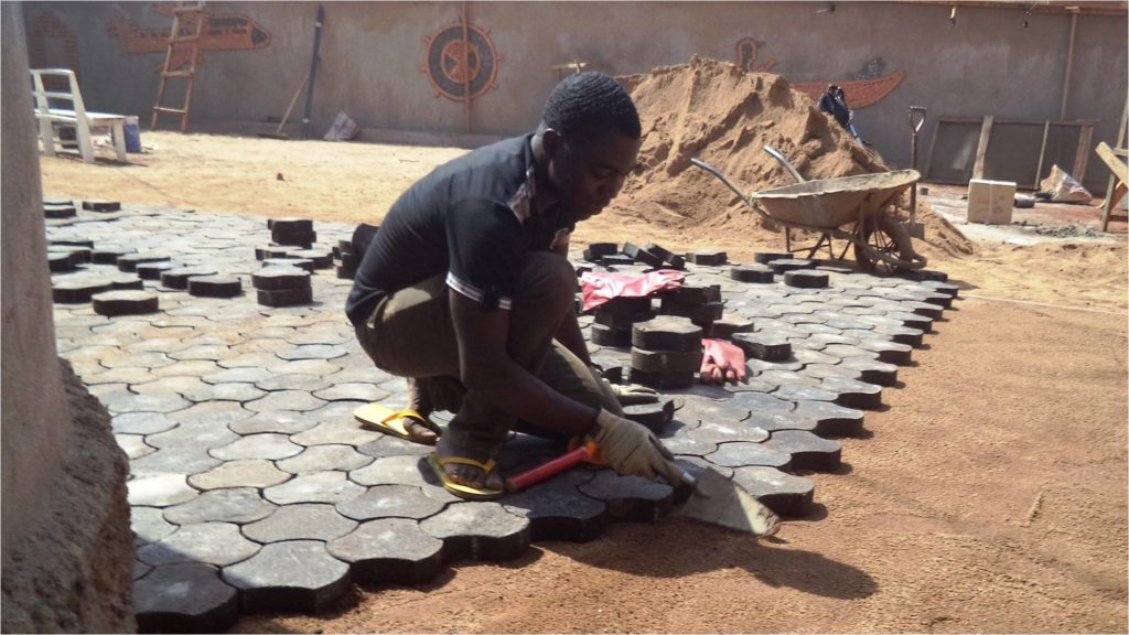 Pierre laying plastic paving tiles
