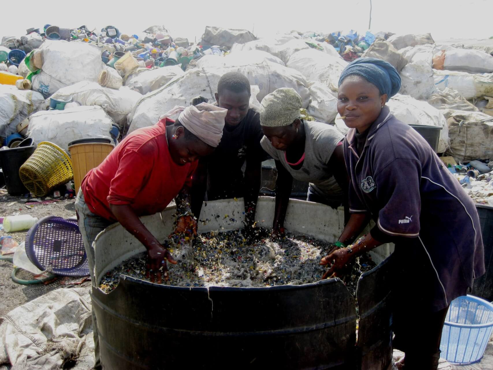 Washing plastic waste flakes, by Sophie van den Berg in Accra, Ghana