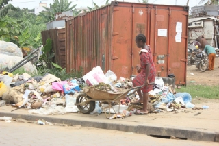 A young girl disposes of her family's rubbish at an informal dumpsite