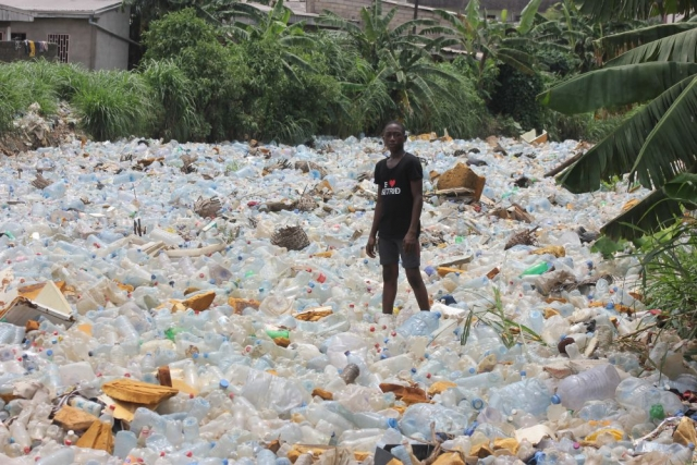 A young man stands in a river of plastic, Douala, Cameroon
