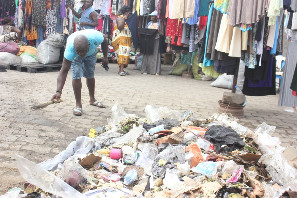 A stallholder gathers the plastic waste from the market in Douala, Cameroon