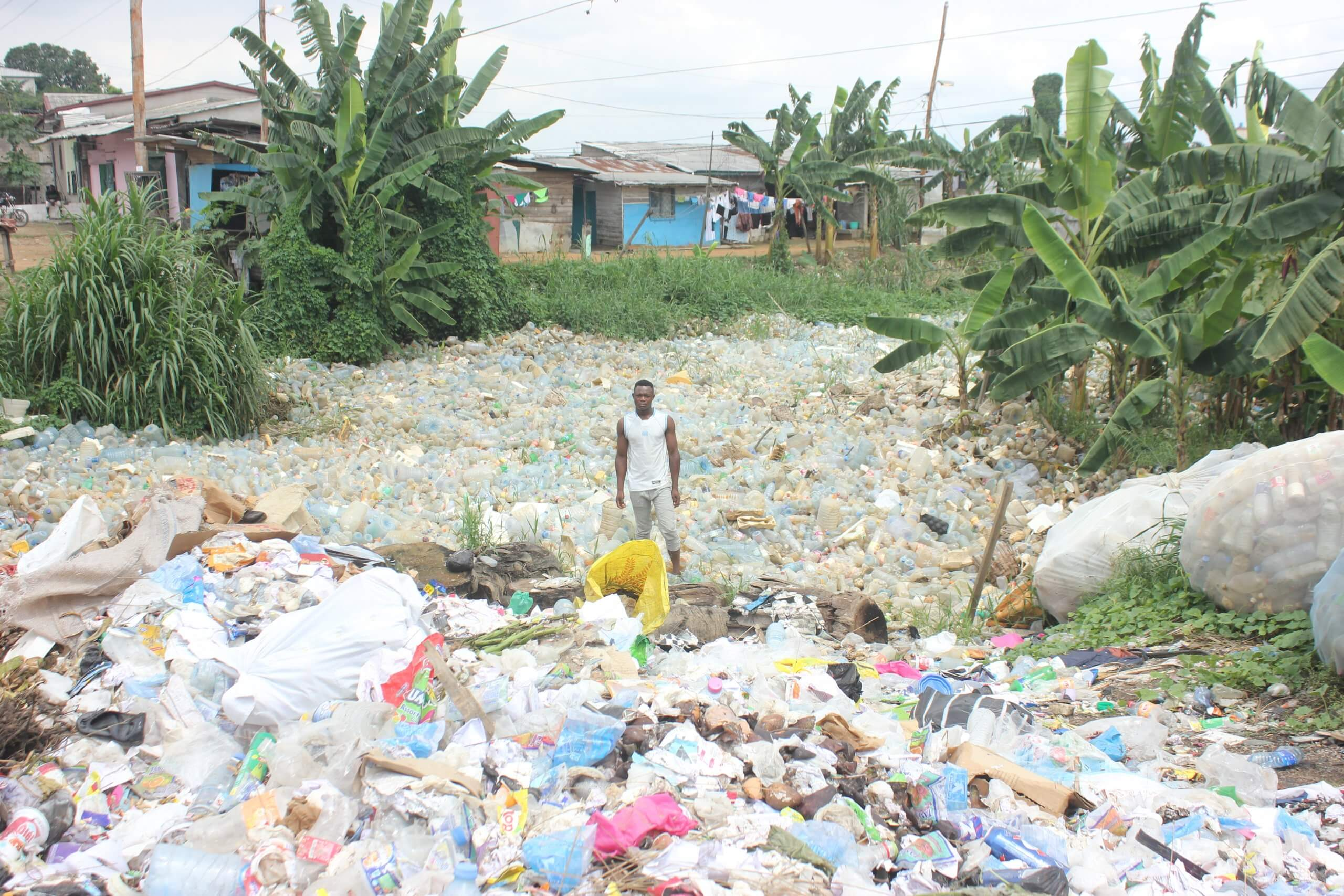 man standing in river of plastic