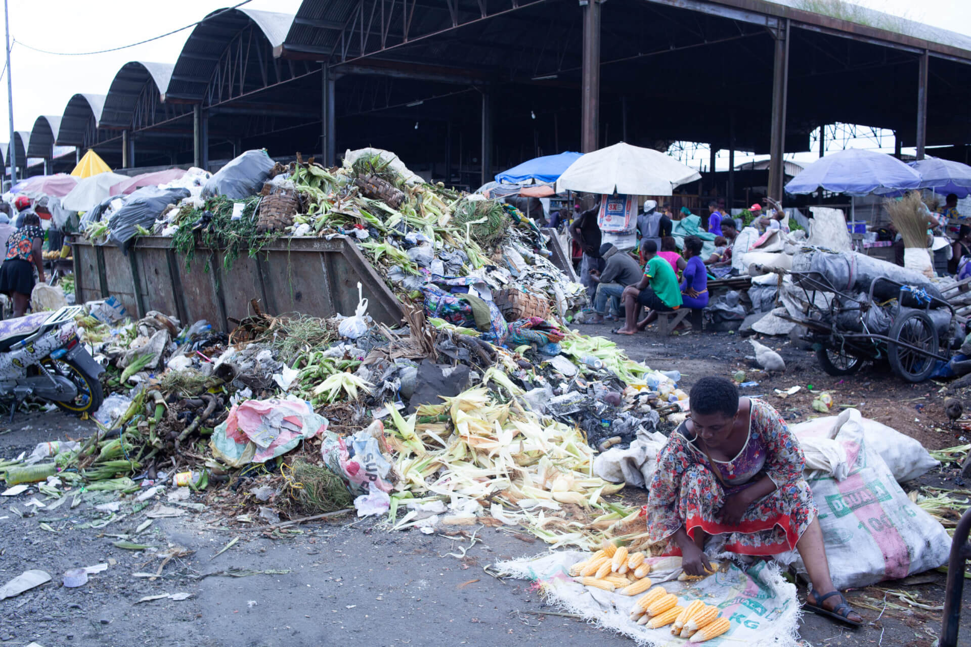 People sell food next to overspilling mixed waste containers