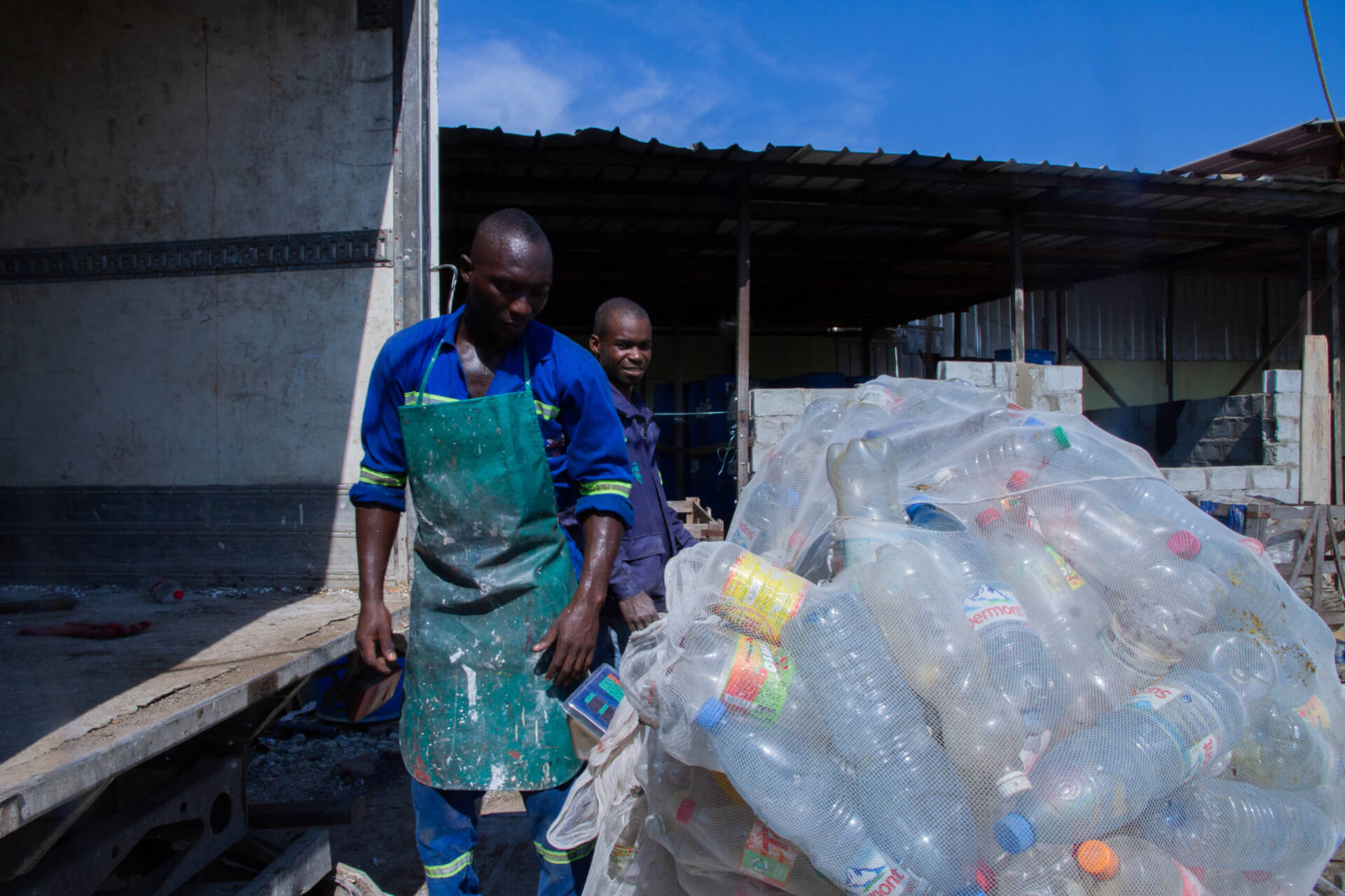 Sacks of PET bottles are unloaded from the truck